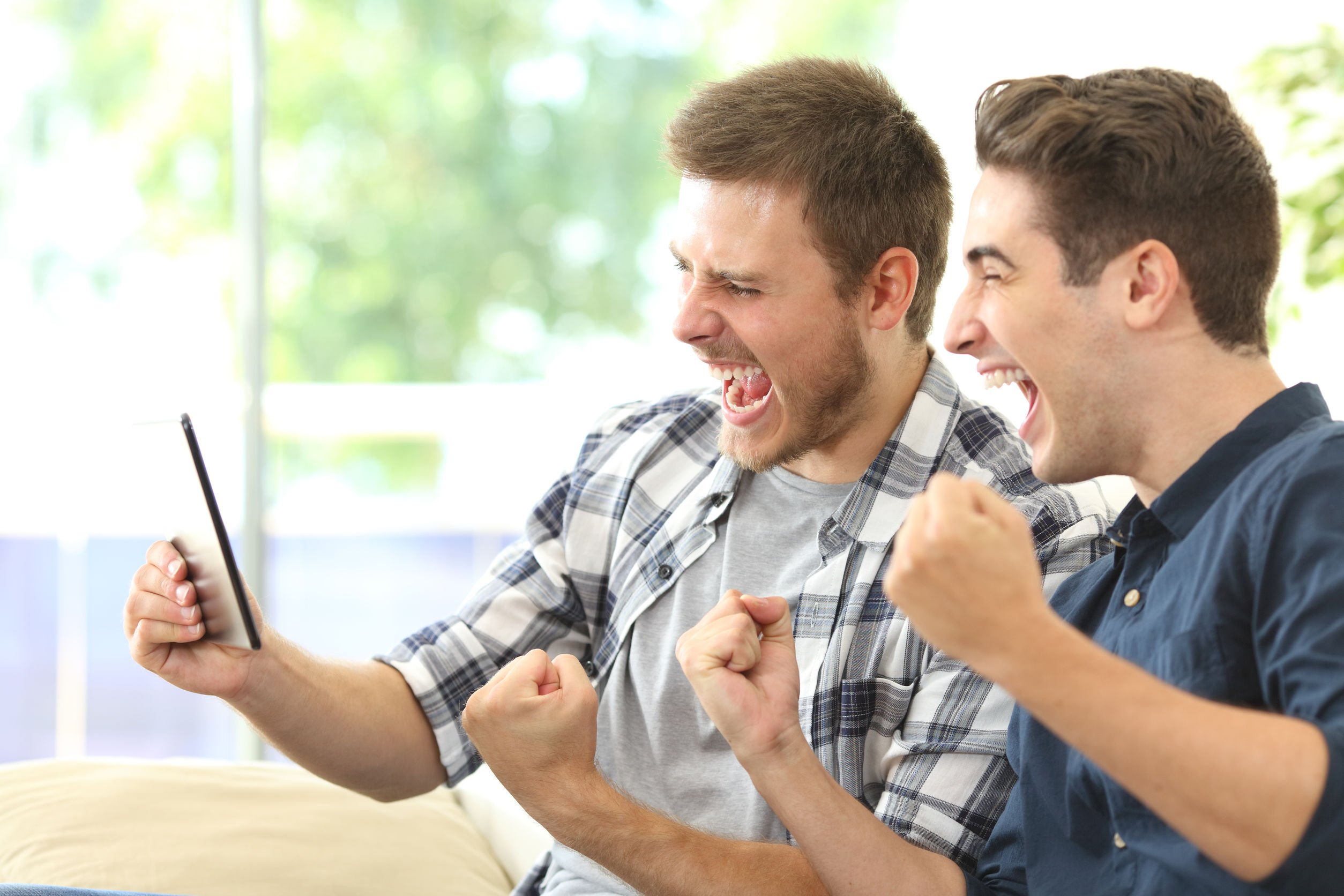 Excited friends watching tv on a tablet
